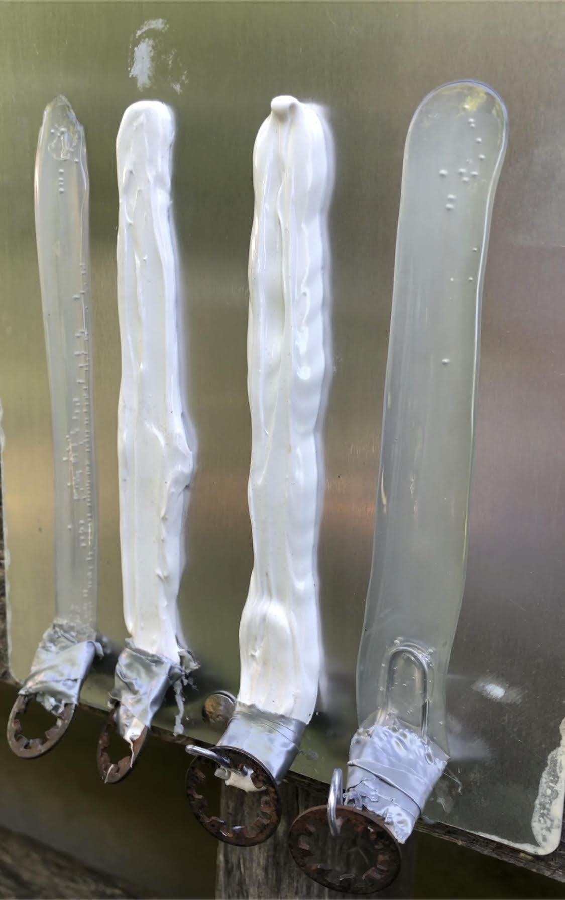 Image of 4 boat sealant strips on aluminum, ready for adhesion testing with a crane scale.